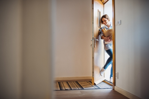 young woman with groceries walking in through front door.